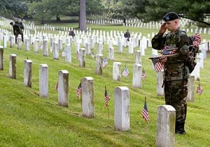 """ARLINGTON, VA - MAY 27:  A member of the U.S. Army Infantry Regiment (The Old Guard), salutes after placing a flag on a grave stone at Arlington National Cemetary May 27, 2004 in Arlington, Virginia. An event called """"Flags In"""" takes place before every Memorial Day weekend in honor of those veterans who have lost their lives.  (Photo by Mark Wilson/Getty Images)"""